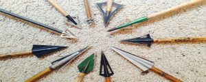 a variety of crossbow broadheads lying on the floor