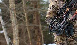 Man hunting in woods with Ravin crossbow