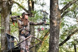 Hunter Shooting From Tree Stand In Forest