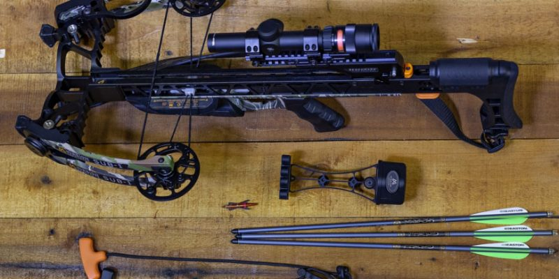 Crossbow with bolts laid out on wooden table
